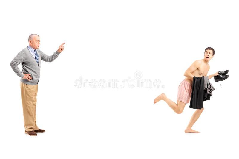Mogen man som bort ropar på en rinnande ung naken man arkivbild