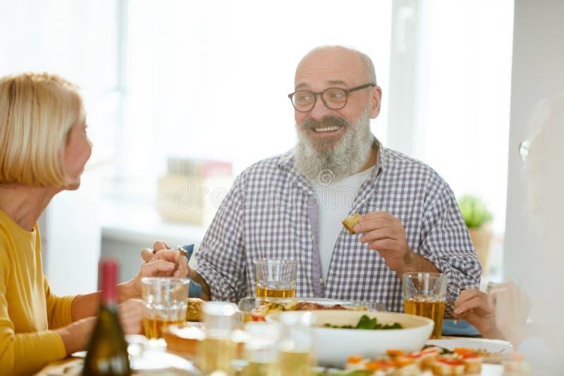 Mogen man som delar uttryck från matställe med frun arkivfoto