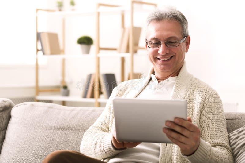 Mogen man som hemma websurfing i digital minnestavla royaltyfri fotografi