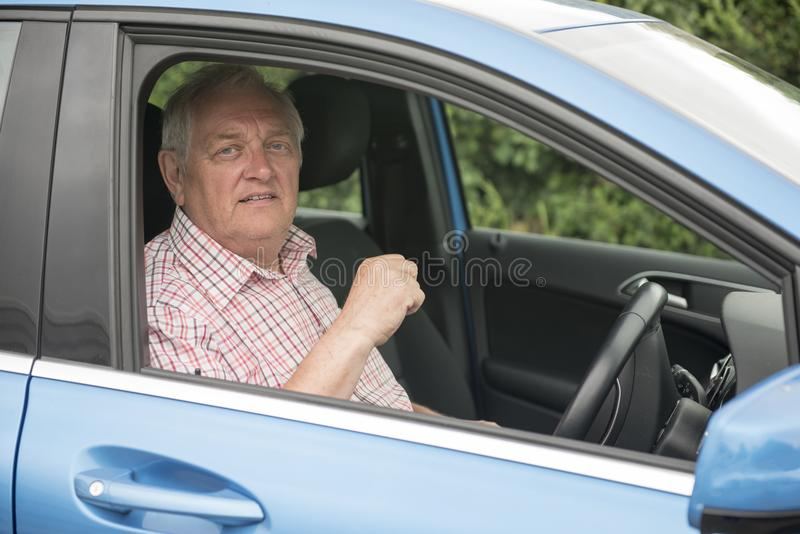 Mogen man som kör i hans bil som ser ilsken fotografering för bildbyråer