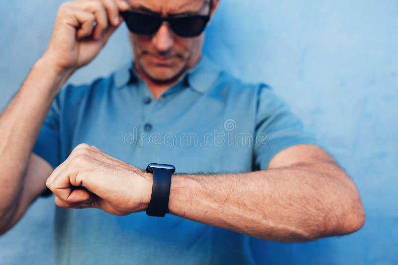 Mogen man som kontrollerar tid på hans armbandsur arkivbild
