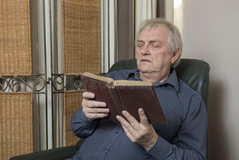 Mogen man som kopplar av och att läsa en bok hemma fotografering för bildbyråer