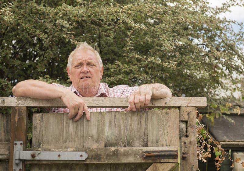 Mogen man som ropar över ett staket i trädgården arkivbilder