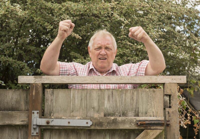 Mogen man som ropar och skakar hans nävar över ett staket royaltyfria bilder