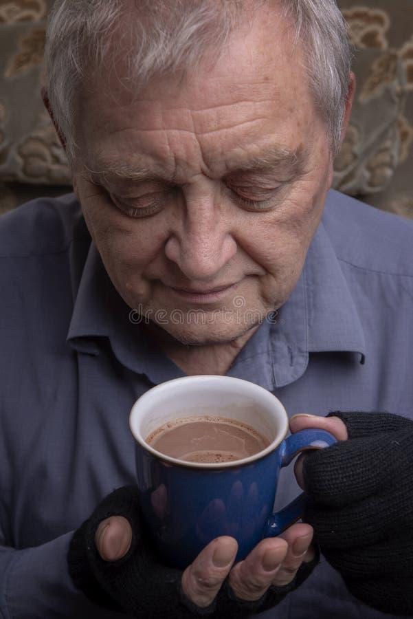 Mogen man som rymmer en kopp av varmt kaffe arkivfoto