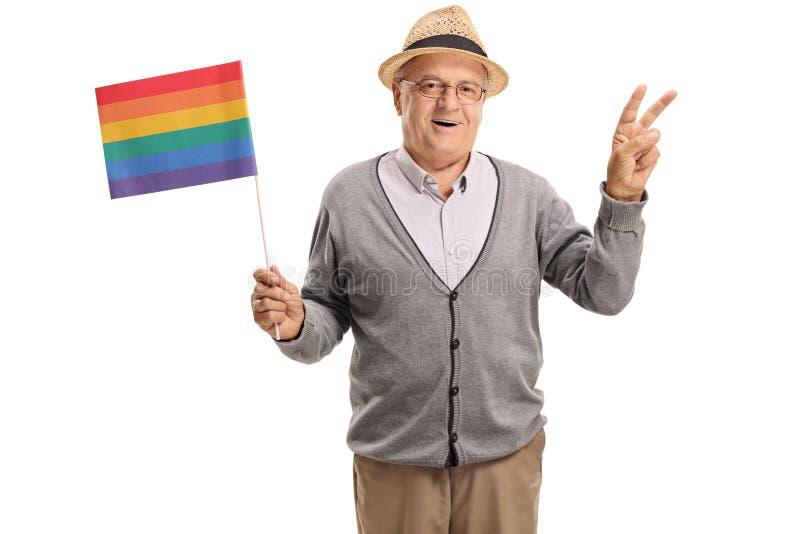 Mogen man som rymmer en regnbågeflagga och gör en fredgest arkivfoto