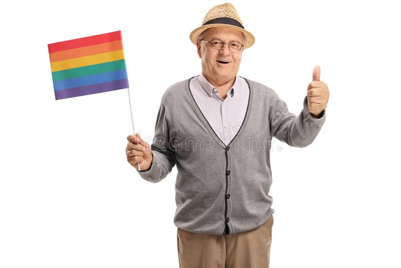 Mogen man som rymmer en regnbågeflagga och gör en tumme upp tecken fotografering för bildbyråer