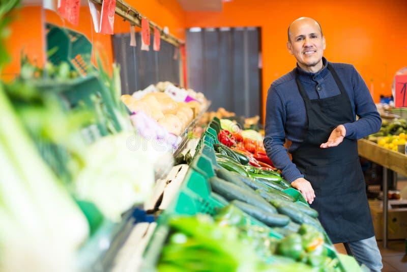 Mogen man som säljer veggies royaltyfria bilder