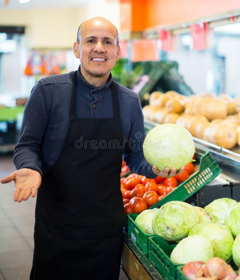 Mogen man som säljer veggies arkivbild