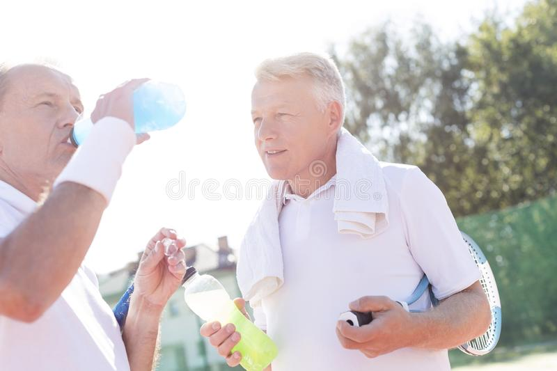Mogen man som ser den höga vännen som dricker från flaskan, medan stå på tennisbanan under sommar royaltyfria bilder
