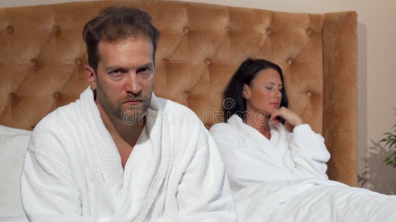 Mogen man som ser till kameran, når att ha grälat med hans fru fotografering för bildbyråer
