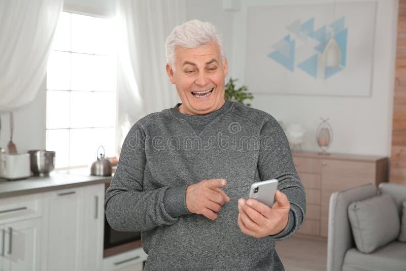 Mogen man som skrattar stund genom att använda smartphonen arkivbilder