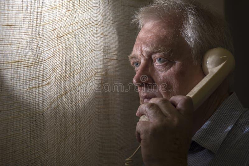 Mogen man som talar på telefonen med skuggor på hans framsida arkivbild