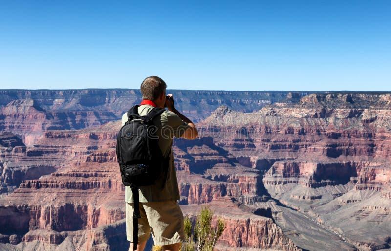Mogen man som tar foto av Grand Canyon under sommarseaso arkivbilder