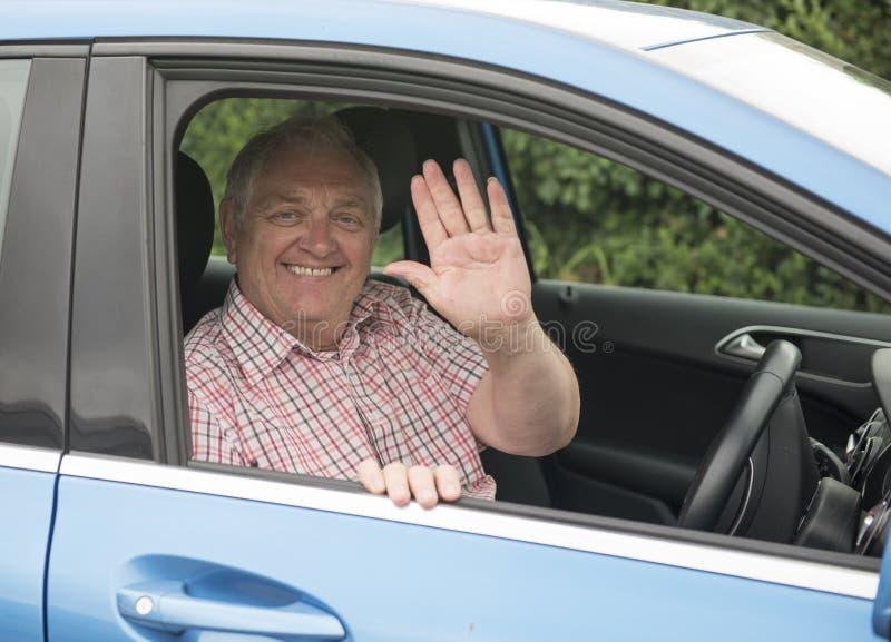 Mogen man som vinkar från hans bilfönster royaltyfria bilder