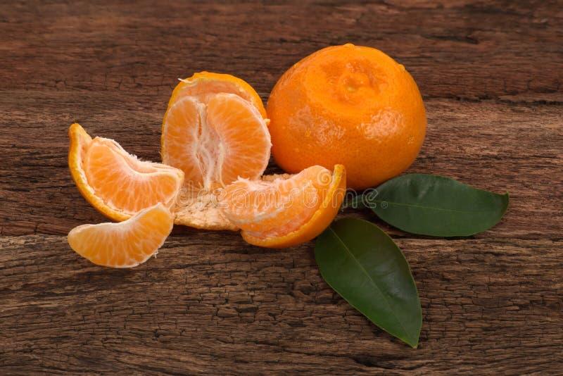 Mogen mandarinfrukt med sidor och ett skalat öppet arkivfoton