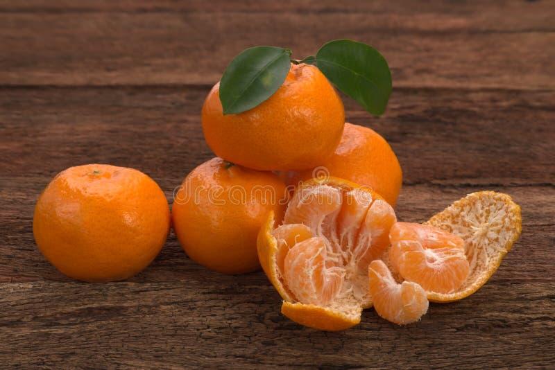 Mogen mandarinfrukt med sidor och ett skalat öppet arkivbilder
