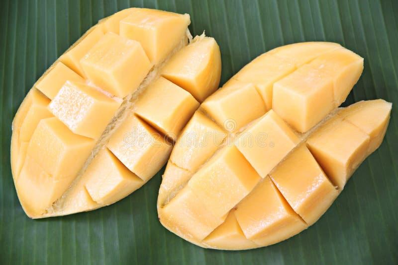 Mogen mango med skivor på banansidor. royaltyfri foto