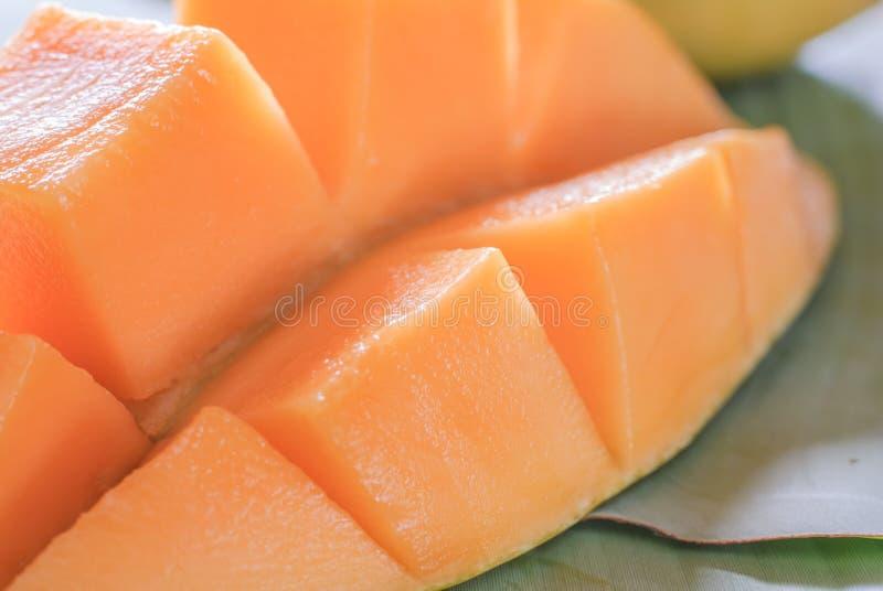 Mogen mango med skivor på banansidor royaltyfri bild