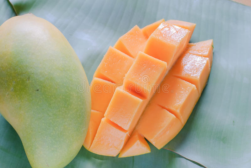 Mogen mango med skivor på banansidor royaltyfria foton