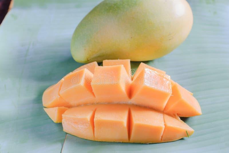 Mogen mango med skivor på banansidor royaltyfria bilder