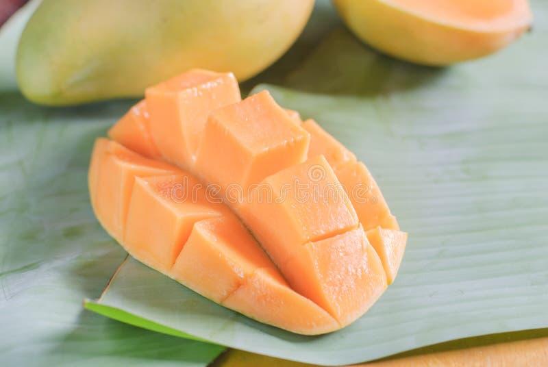 Mogen mango med skivor på banansidor arkivbild