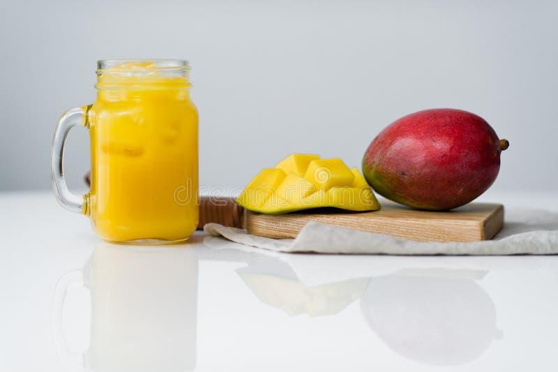 Mogen mango och ett exponeringsglas av mangofruktsaft p? en tr?sk?rbr?da royaltyfria foton