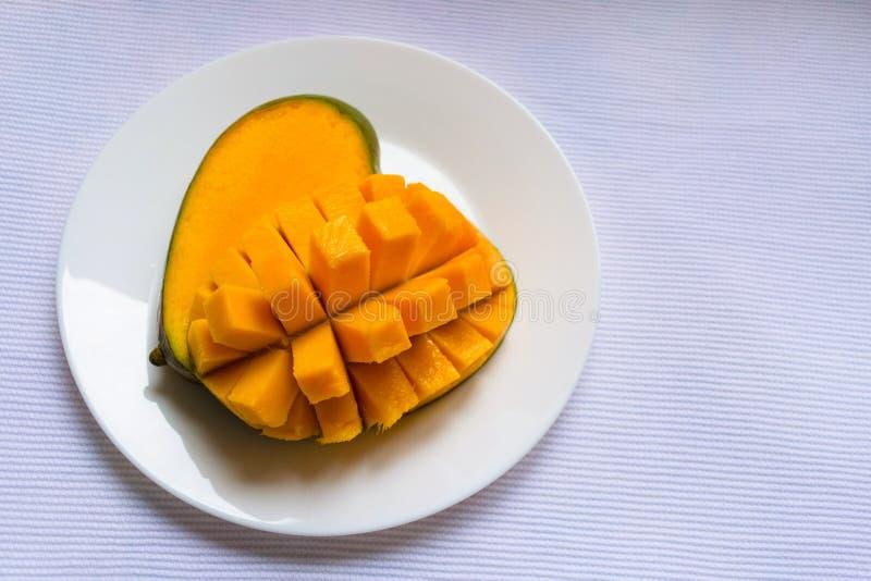 Mogen mango som tärnas på en vit platta kopiera avst?nd royaltyfri fotografi