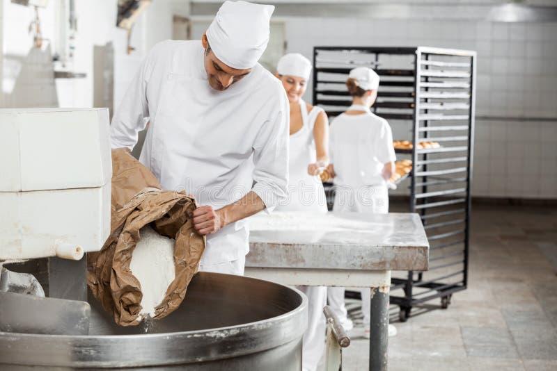 Mogen manlig bagare Pouring Flour In som knådar maskinen royaltyfri foto