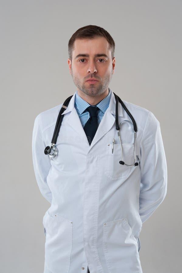 Mogen manlig doktor med allvarligt framsidaanseende på grå bakgrund royaltyfri bild