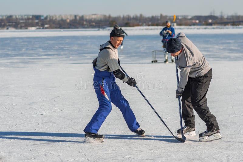 Mogen manstridighet för packen, medan spela hockey på en djupfryst flod Dnepr arkivbild