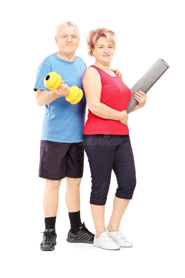Mogen matta man och kvinna som poserar med hanteln och arkivbild