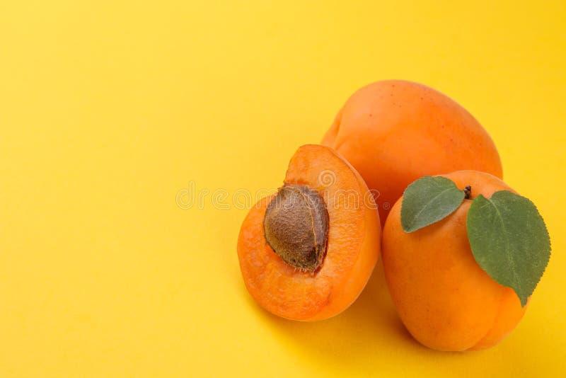 Mogen ny aprikos med ett blad p? en ljus pappersgulingbakgrund med ett st?lle f?r en inskrift arkivfoton