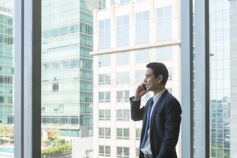 Mogen och säker affärsledare som ser se ut ur stora fönster på en sikt av staden under arkivbilder