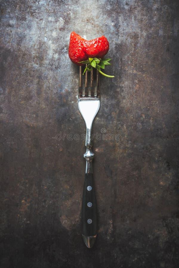 Mogen och saftig biten jordgubbe på gaffeln royaltyfria foton