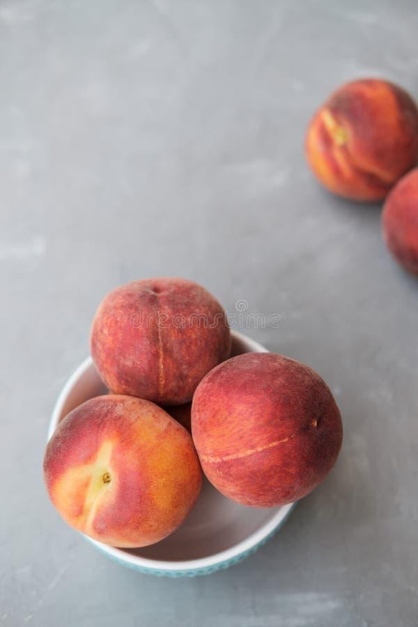 Mogen organisk persika i blå keramisk bunke i grå bakgrund arkivfoton