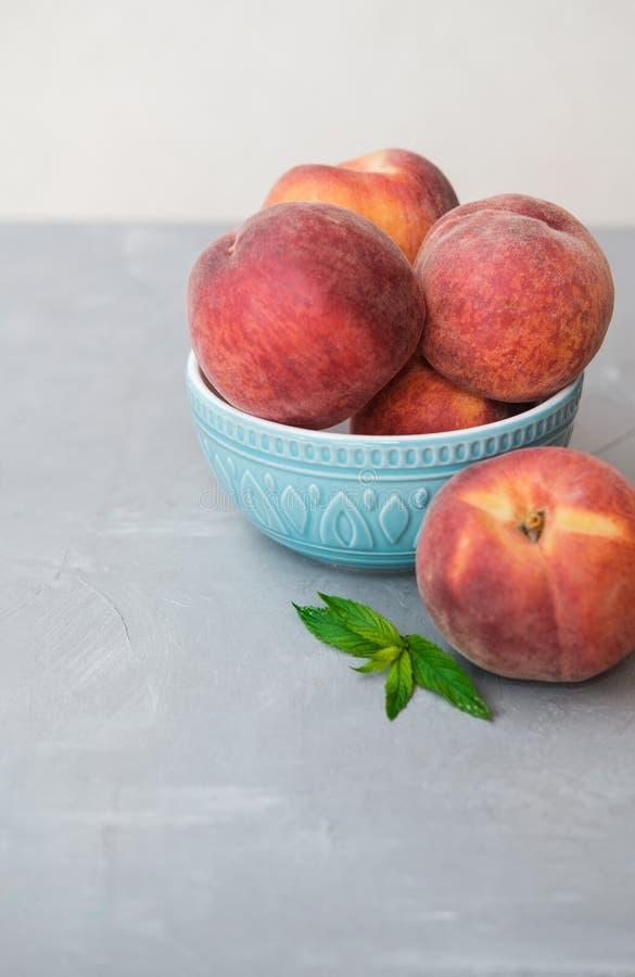 Mogen organisk persika i blå keramisk bunke i grå bakgrund fotografering för bildbyråer