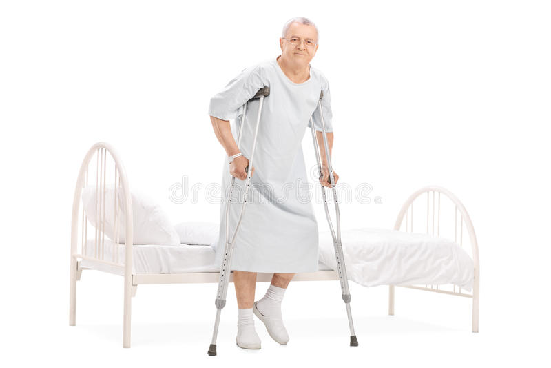 Mogen patient med kryckor som får ut ur säng royaltyfria bilder