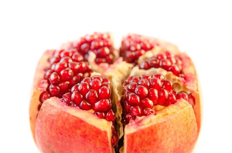 Mogen röd granatäpple och frönärbild i förgrund som isoleras på vit bakgrundsut-av-fokus suddig makro arkivbilder