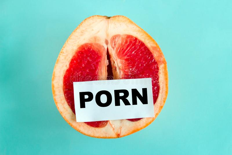 Mogen saftig grapefrukt med anmärkningspornografi som isoleras på en blå bakgrund royaltyfri bild