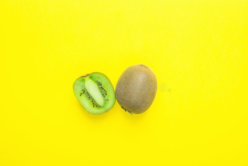 Mogen saftig hel och halverad kiwi på heltäckandegulingbakgrund Sunda vitaminer bantar tropiska frukter för sommarDetoxstrikt veg royaltyfri fotografi