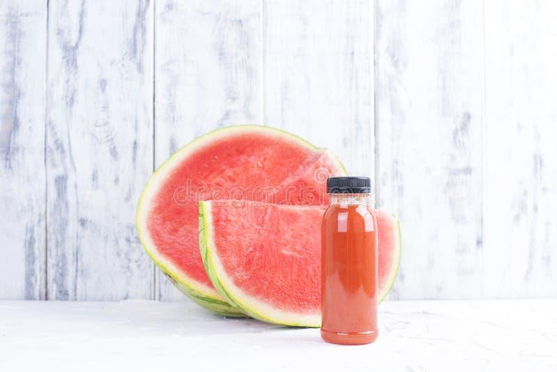 Mogen saftig vattenmelon och ny fruktsaft i en plast- flaska kopiera avstånd arkivfoto