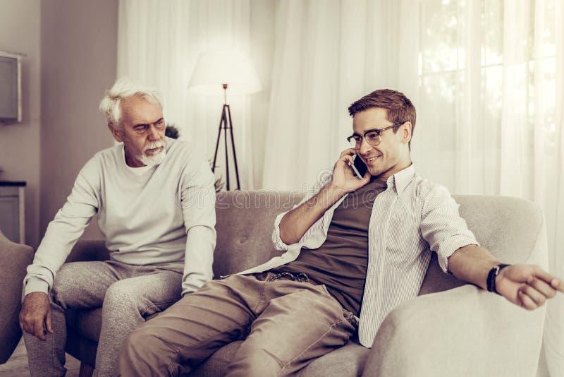 Mogen son som talar över telefonen medan fader som sitter på en soffa fotografering för bildbyråer