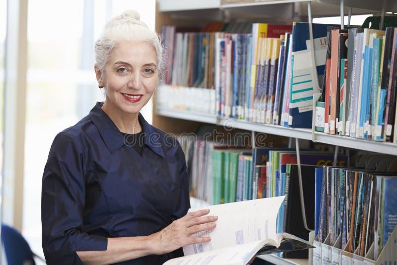 Mogen student Studying In Library för kvinnlig royaltyfri foto