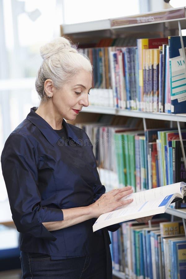 Mogen student Studying In Library för kvinnlig arkivfoto