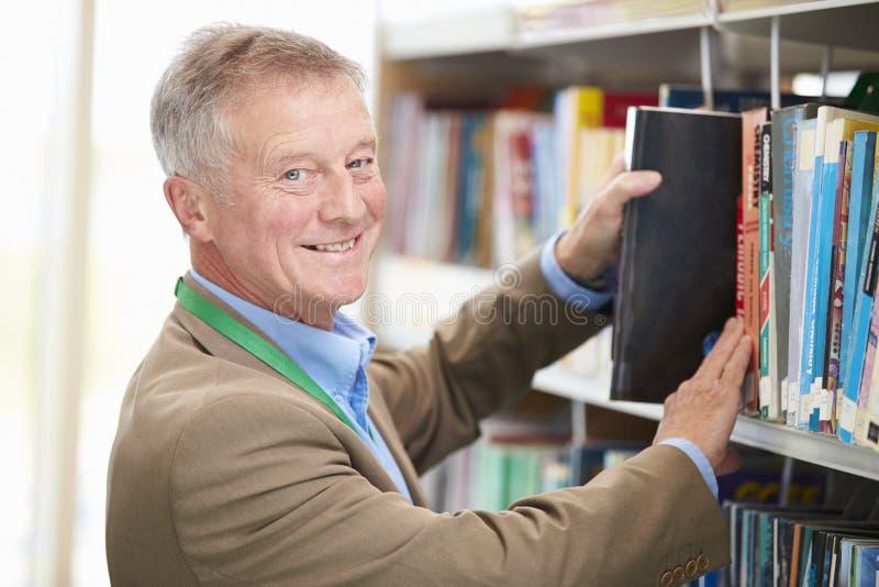 Mogen student Studying In Library för man royaltyfria bilder