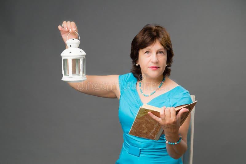 Mogen studentkvinna med boken och lyktan royaltyfri fotografi