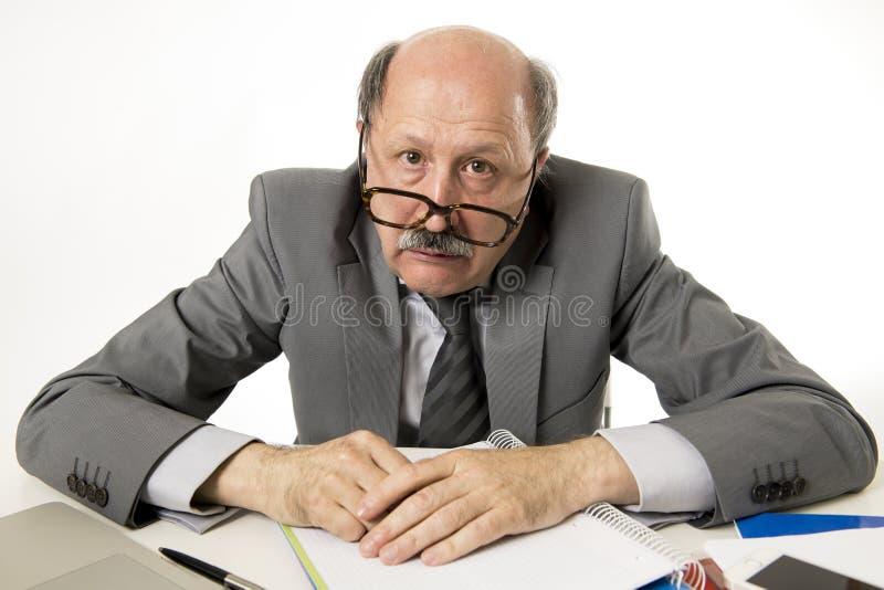 Mogen upptagen affärsman för pensionär med flinten på hans funktionsdugliga stressat för 60-tal och frustrerat på skrivbordet för royaltyfri bild