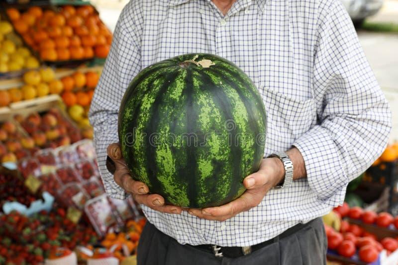Mogen vattenmelon i händerna av säljaren av den grekiska grönsakfruktaffären royaltyfri bild