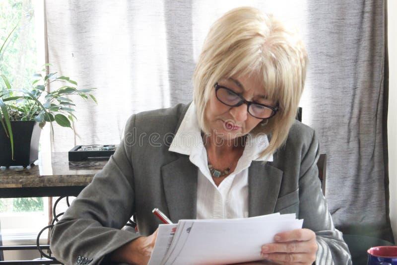 Mogen vuxen affärskvinna som studerar dokument i ett kontor. royaltyfri foto